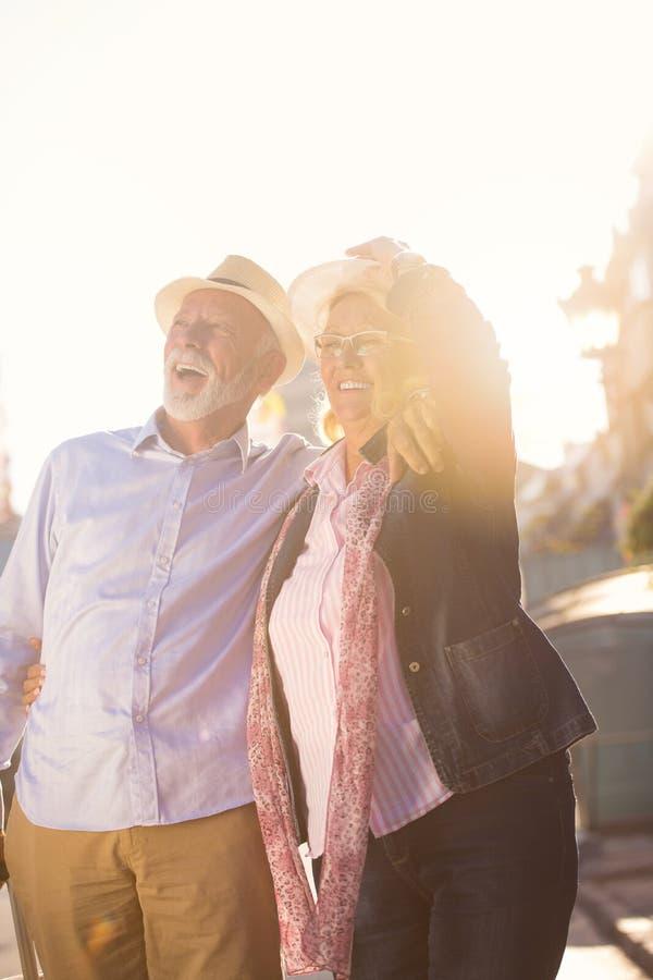Pares mayores alegres felices de turistas con la guía del mapa y de la ciudad que camina en la calle imagen de archivo