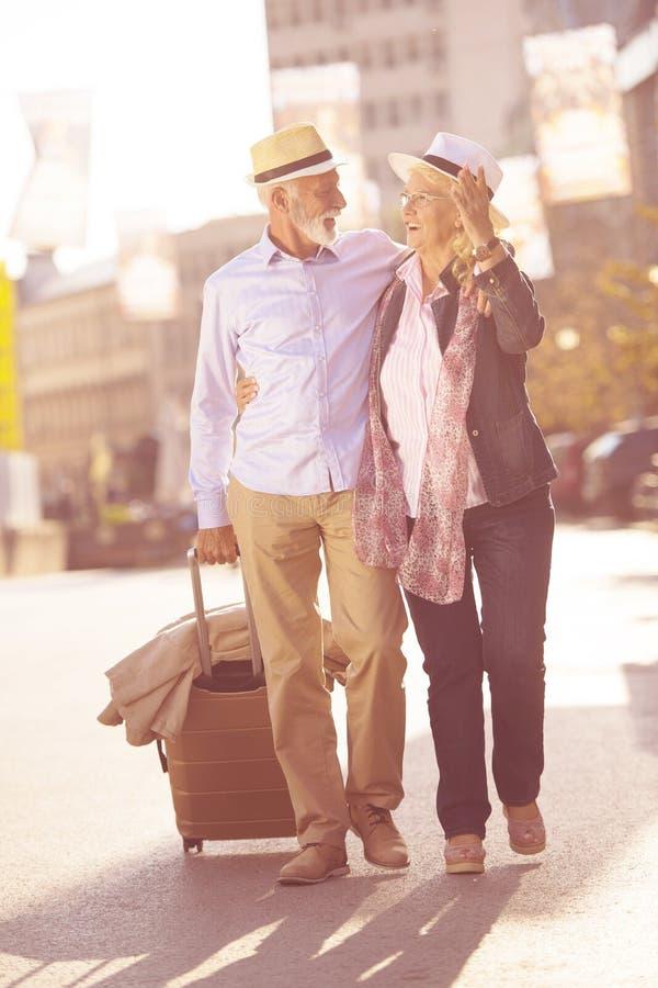 Pares mayores alegres felices de turistas con la guía del mapa y de la ciudad que camina en la calle imagen de archivo libre de regalías