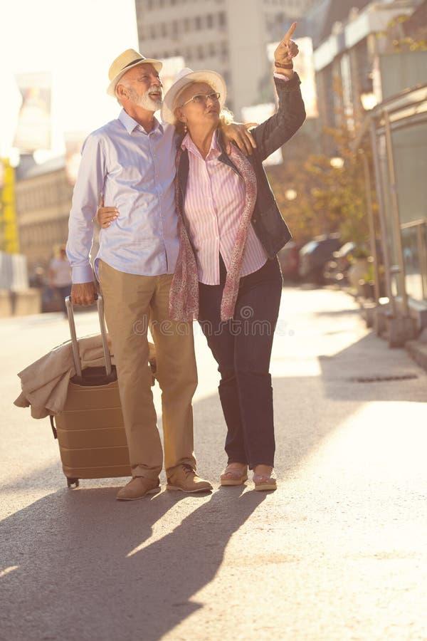 Pares mayores alegres felices de turistas con la guía del mapa y de la ciudad que camina en la calle foto de archivo