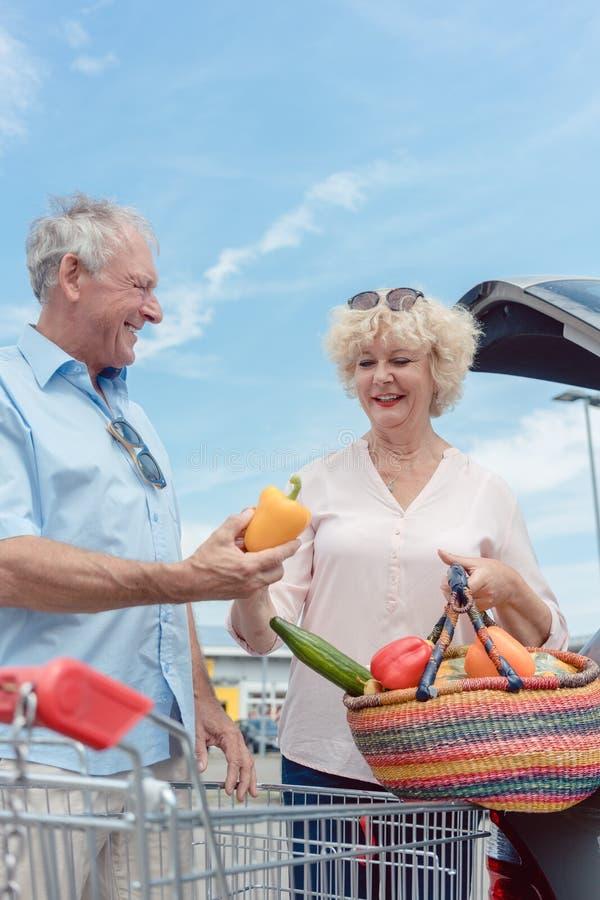 Pares mayores alegres felices para comprar verduras frescas del th imagen de archivo