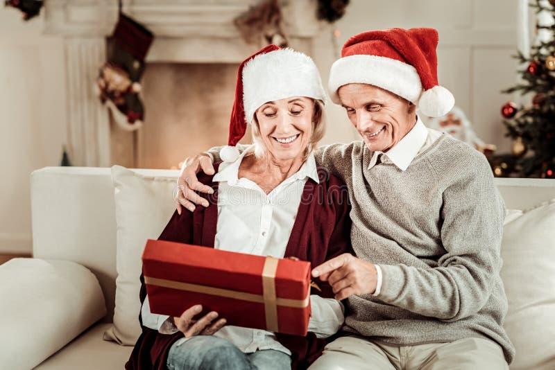Pares mayores alegres que sientan y que sostienen un regalo imagen de archivo