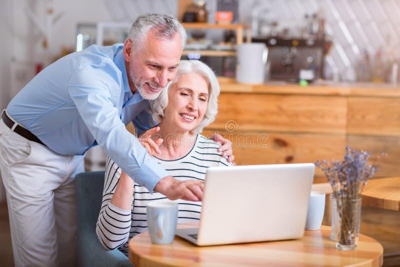 Pares mayores alegres usando el ordenador portátil imagen de archivo