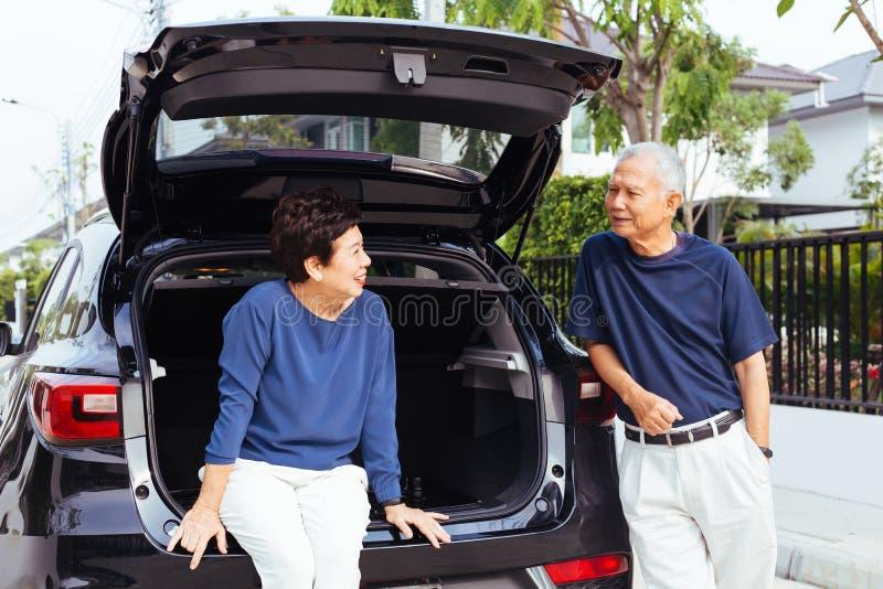 Pares mayores asiáticos felices que se colocan en la parte de atrás del coche de SUV, mirando uno a con sonrisa y felicidad fotografía de archivo