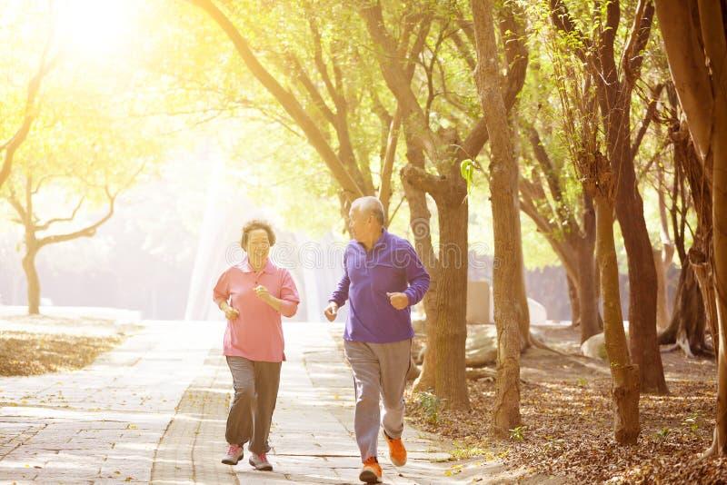 pares mayores asiáticos que ejercitan en el parque foto de archivo