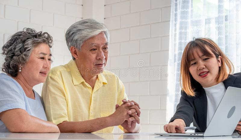 Pares mayores asi?ticos con el consejero financiero sobre el documento del impuesto y del retiro en casa concepto feliz del envej imagen de archivo libre de regalías