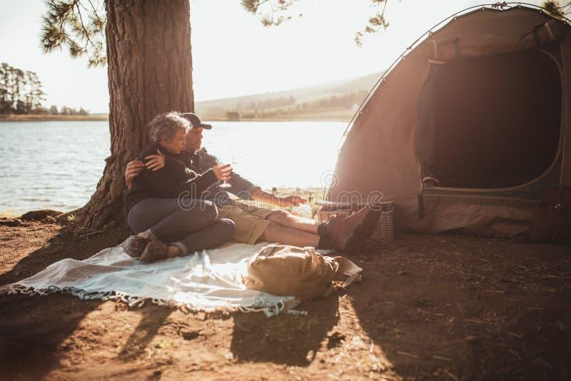 Pares mayores cariñosos que acampan cerca de un lago fotos de archivo libres de regalías
