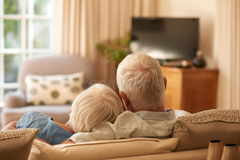 Pares mayores cariñosos que se relajan junto en su sofá en casa fotos de archivo libres de regalías