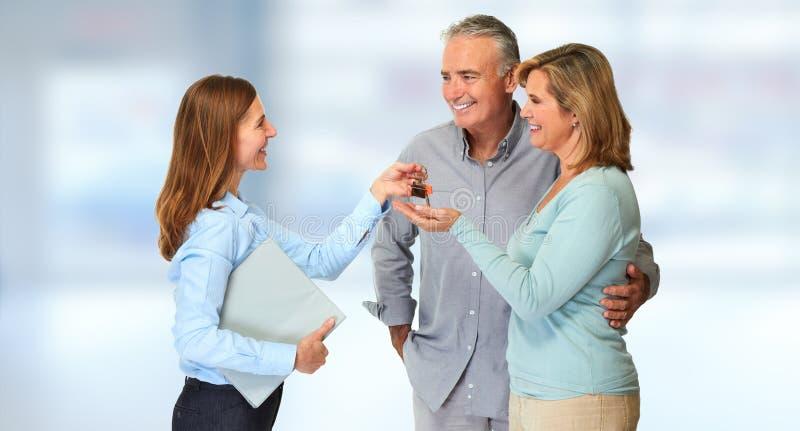 Pares mayores con el agente de la propiedad inmobiliaria imagen de archivo libre de regalías