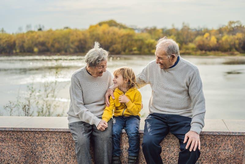 Pares mayores con el nieto del bebé en el parque del otoño Bisabuela, bisabuelo y grande-nieto foto de archivo