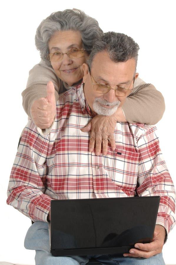 Pares mayores con el ordenador portátil foto de archivo