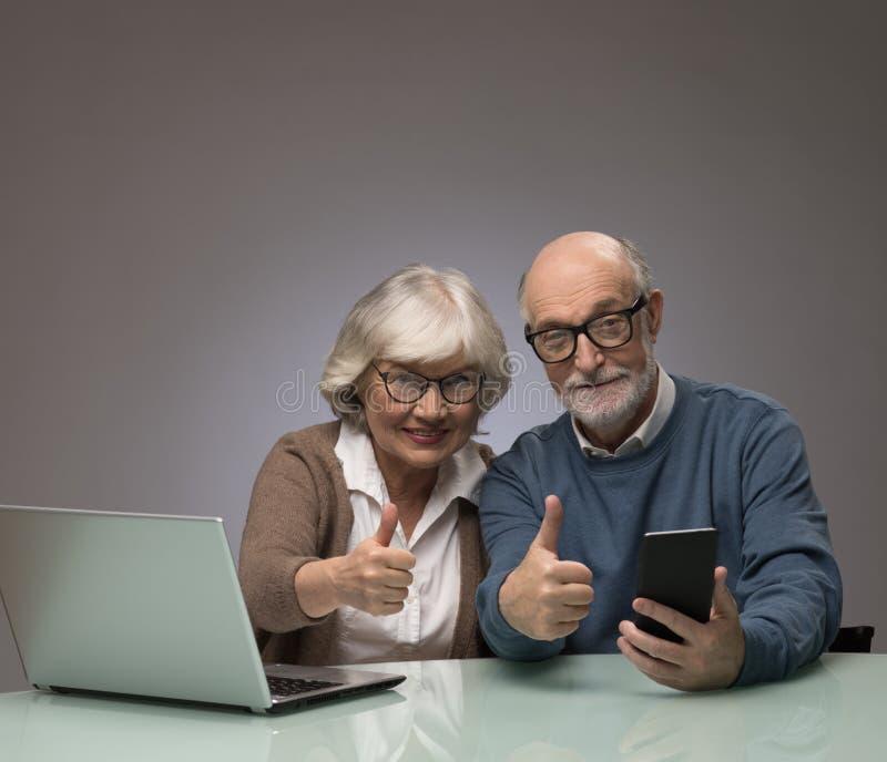 Pares mayores con el ordenador portátil y el smartphone fotos de archivo