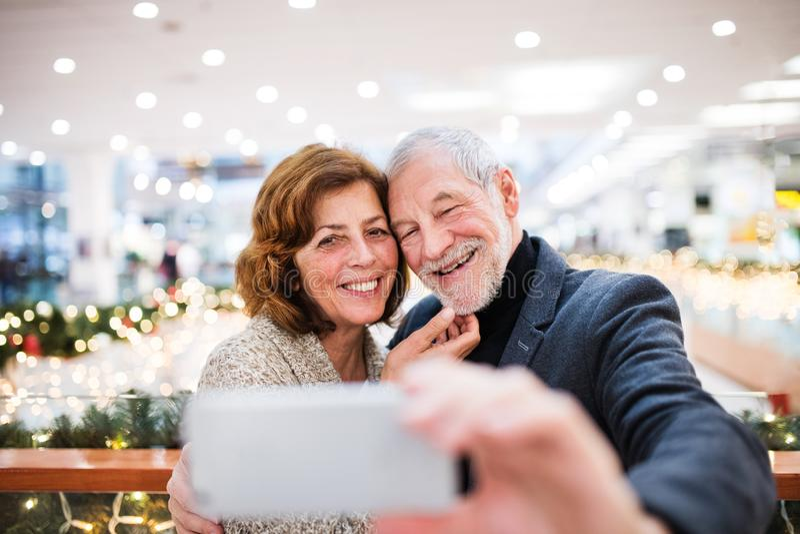 Pares mayores con el smartphone que hace compras de la Navidad fotos de archivo libres de regalías