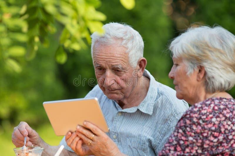 Pares mayores con el tabet en jardín imagenes de archivo