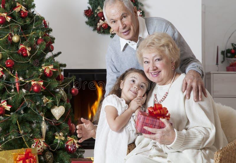 Pares mayores con la nieta que celebra la Navidad foto de archivo libre de regalías