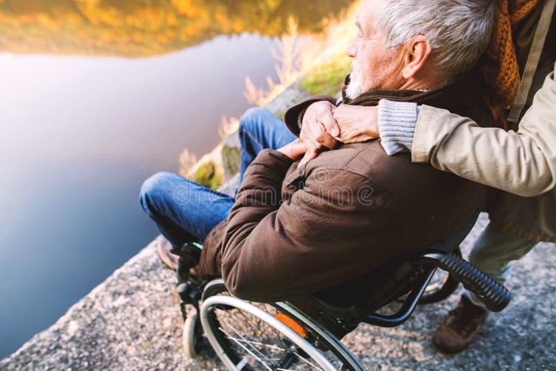Pares mayores con la silla de ruedas en naturaleza del otoño fotos de archivo libres de regalías