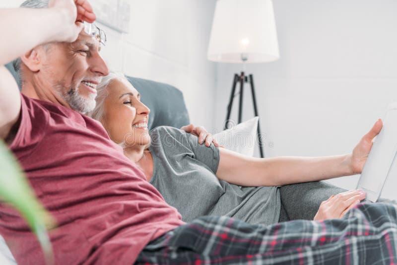 Pares mayores con la tableta digital que descansa en cama junto imagen de archivo libre de regalías