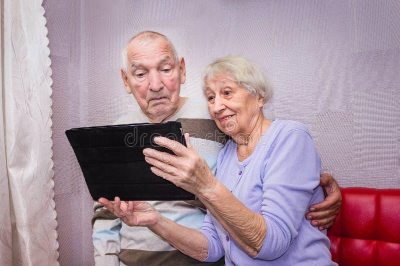 Pares mayores con la tableta que se relaja en casa foto de archivo