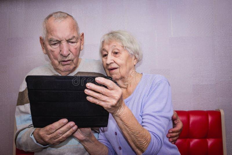 Pares mayores con la tableta que se relaja en casa fotos de archivo libres de regalías