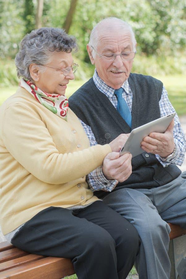 Pares mayores con la tableta foto de archivo libre de regalías