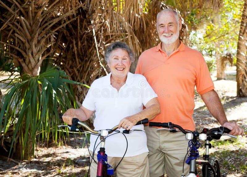 Pares mayores con las bicis foto de archivo libre de regalías