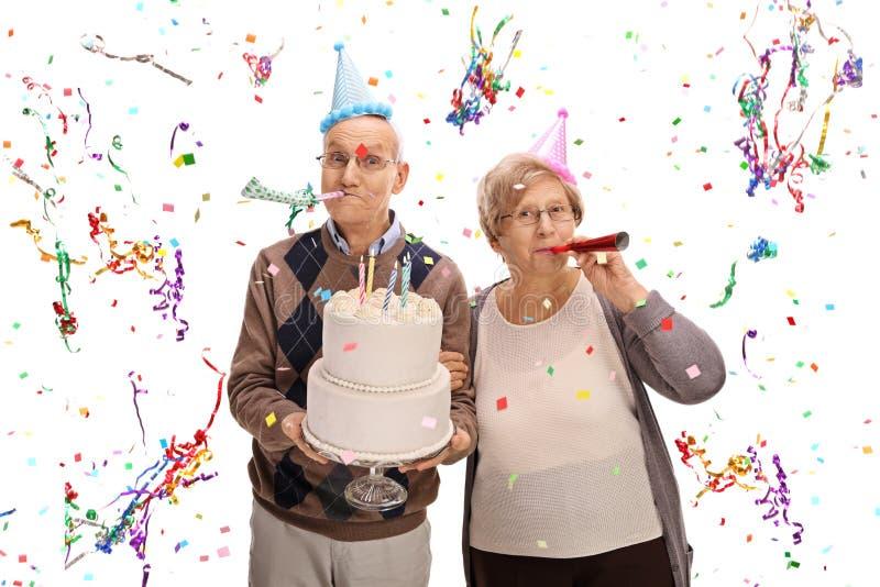 Pares mayores con los cuernos y los sombreros del partido que celebran cumpleaños imagen de archivo libre de regalías