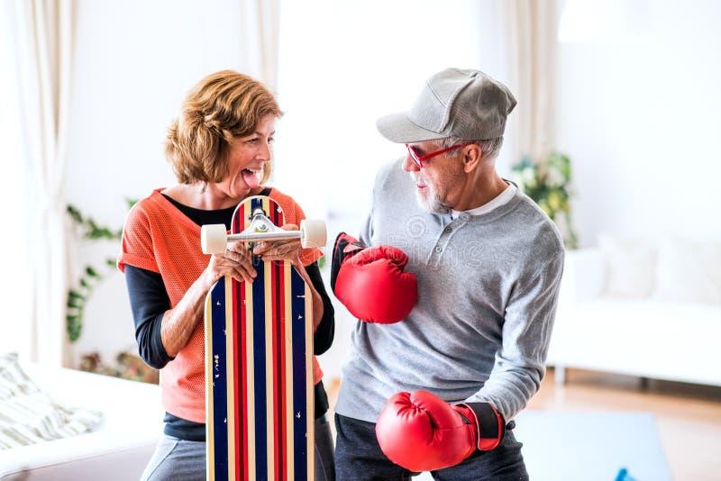 Pares mayores con los guantes de boxeo y longboard que se divierte en casa fotos de archivo