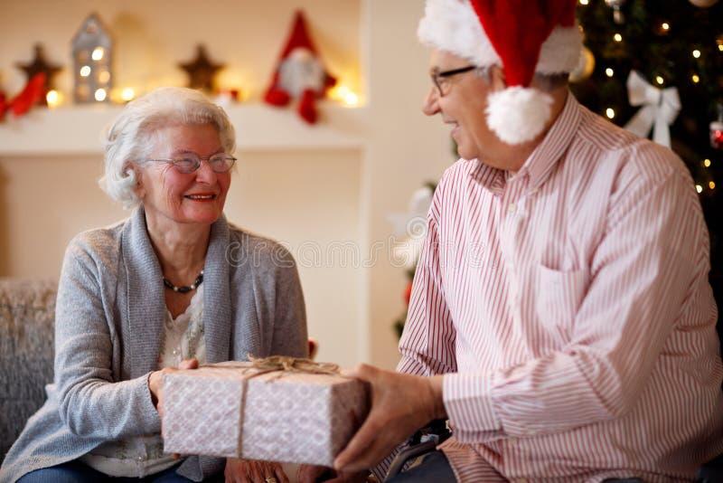 Pares mayores con los presentes que pasan la Navidad junta foto de archivo libre de regalías