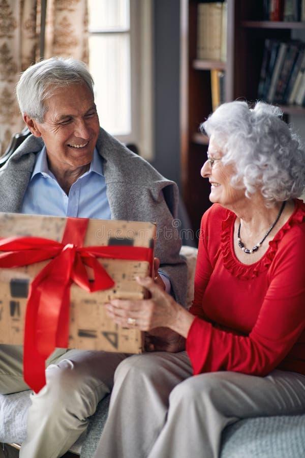 Pares mayores con los presentes que pasan la Navidad junta imágenes de archivo libres de regalías