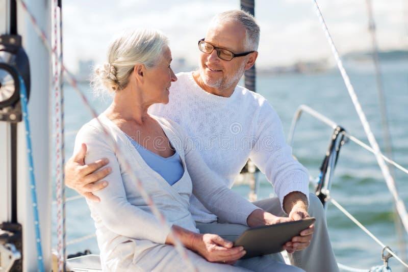 Pares mayores con PC de la tableta en el barco o el yate de vela imagen de archivo