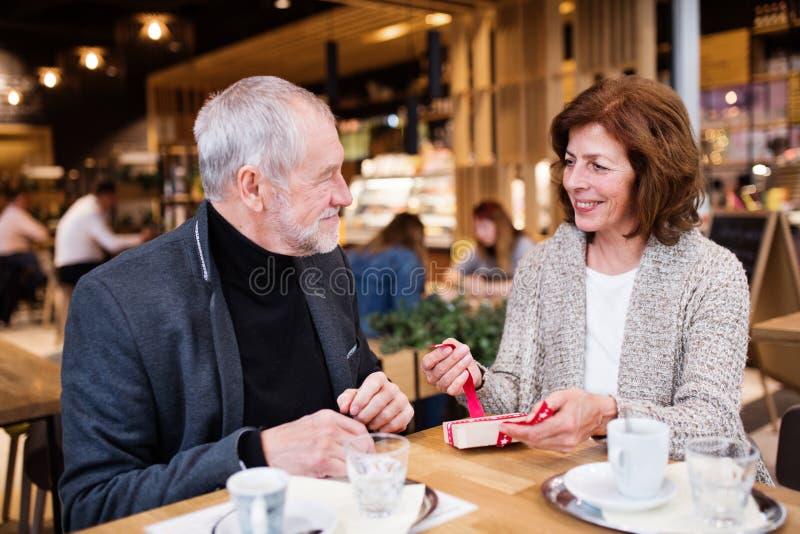 Pares mayores con un presente en un café Tiempo de la Navidad fotografía de archivo libre de regalías