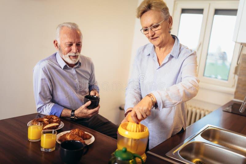 Pares mayores de amor que se divierten que prepara la comida sana en el desayuno en la cocina fotos de archivo libres de regalías