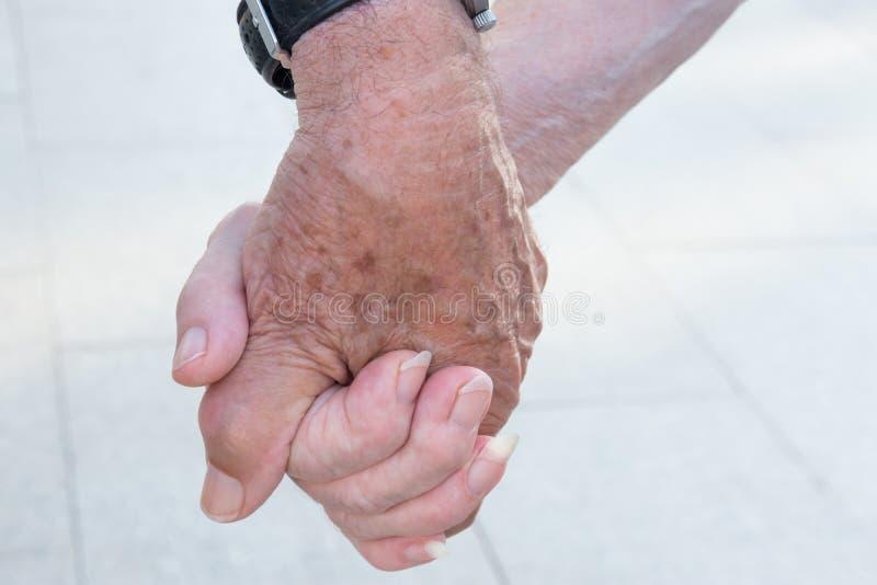 Pares mayores de la gente mayor que llevan a cabo las manos que caminan en la calle Unidad romántica Fidelity de la dedicación de fotos de archivo libres de regalías