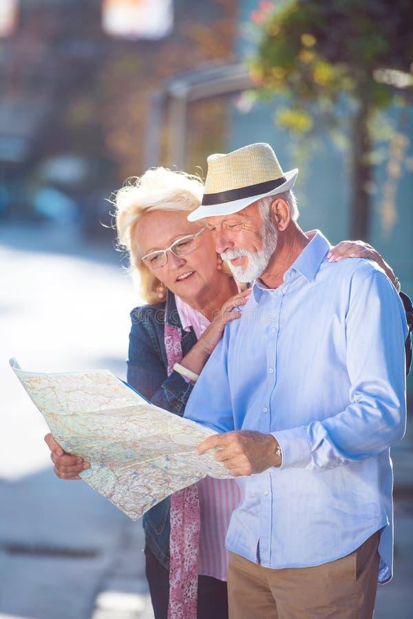 Pares mayores de los turistas que miran el mapa de la ciudad imágenes de archivo libres de regalías