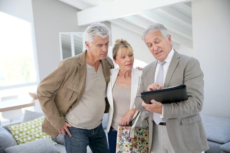 Pares mayores de moda con el agente inmobiliario que visita la nueva casa imagenes de archivo