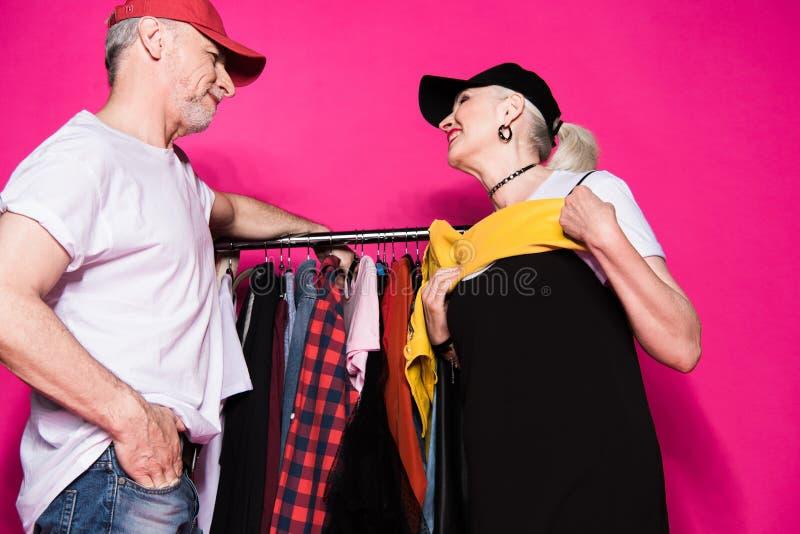 Pares mayores de moda felices que se colocan que eligen la ropa fotos de archivo