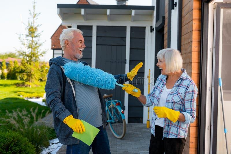 Pares mayores de risa que se divierten mientras que hace la limpieza cerca de casa de verano imagen de archivo