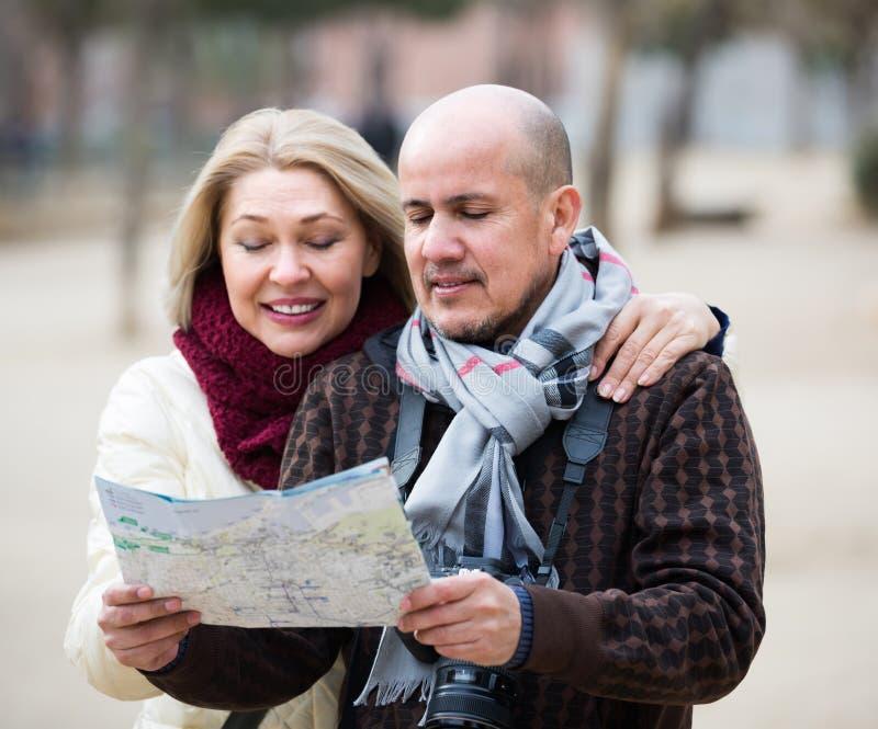 Pares mayores de viajeros con el mapa foto de archivo