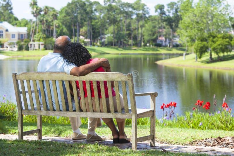 Pares mayores del afroamericano en banco de parque foto de archivo libre de regalías
