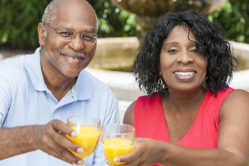Pares mayores del afroamericano que beben el zumo de naranja imagenes de archivo