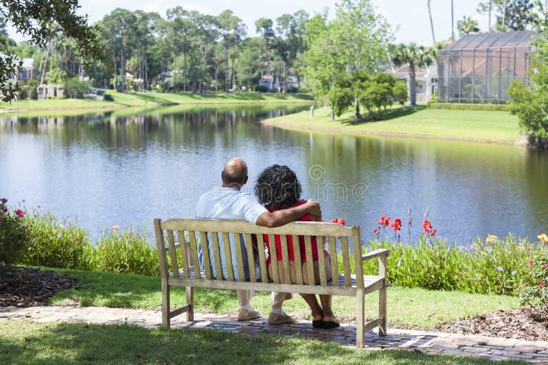 Pares mayores del afroamericano que se sientan en banco de parque imagen de archivo