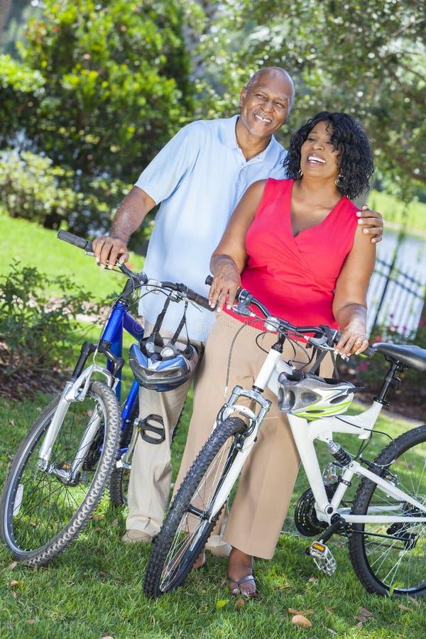 Pares mayores del hombre de la mujer del afroamericano en las bicis fotografía de archivo