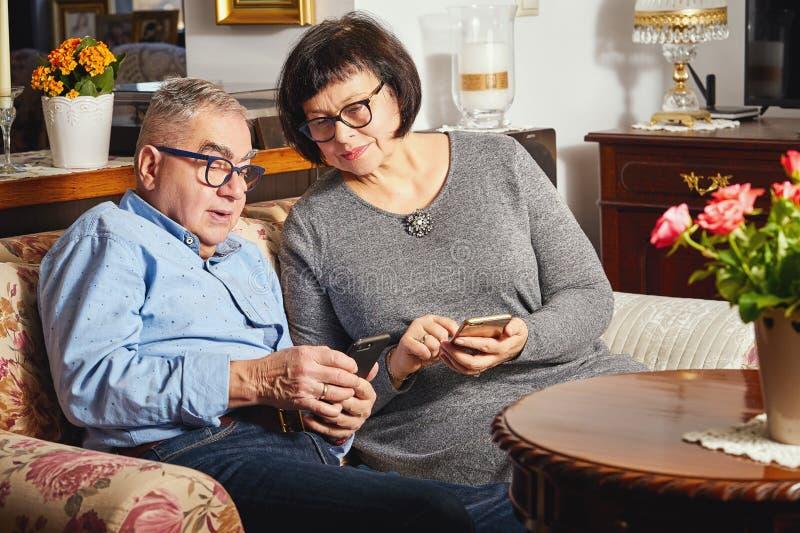 Pares mayores del matrimonio que practican surf la red con el teléfono móvil mientras que se sienta en el sofá foto de archivo libre de regalías