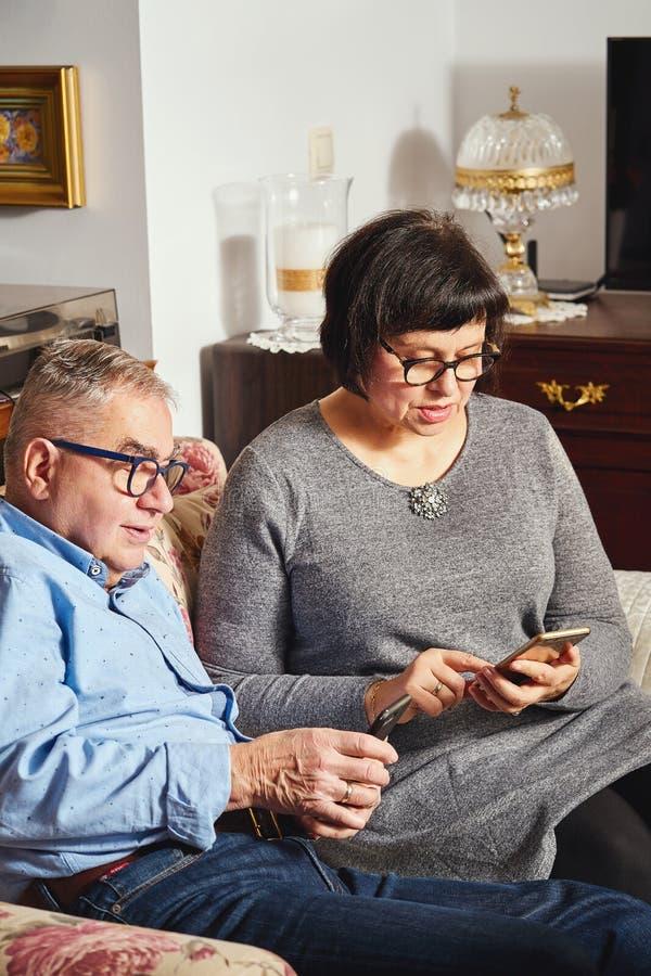 Pares mayores del matrimonio que practican surf la red con el teléfono móvil mientras que se sienta en el sofá foto de archivo