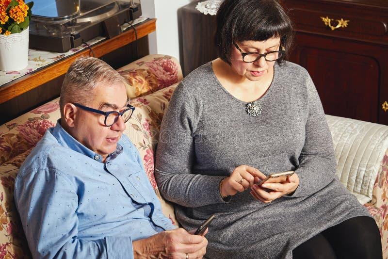 Pares mayores del matrimonio que practican surf la red con el teléfono móvil mientras que se sienta en el sofá imagenes de archivo