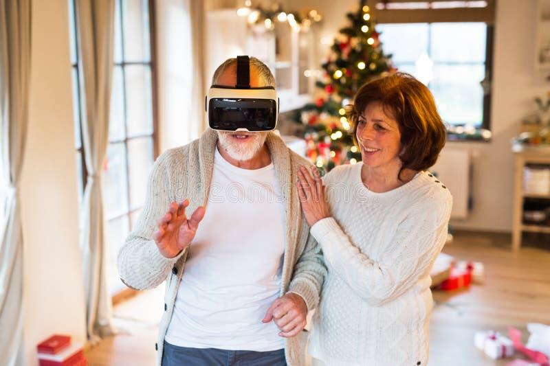 Pares mayores delante del árbol de navidad con las gafas de VR fotografía de archivo
