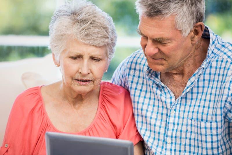 Pares mayores dudosos usando la tableta imagen de archivo libre de regalías