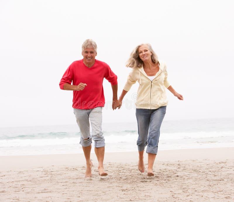 Pares mayores el el día de fiesta que se ejecuta a lo largo de la playa imagen de archivo libre de regalías