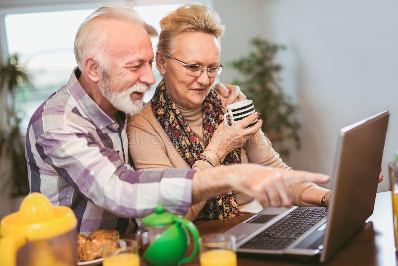 Pares mayores emocionados que miran un ordenador portátil junto imagen de archivo
