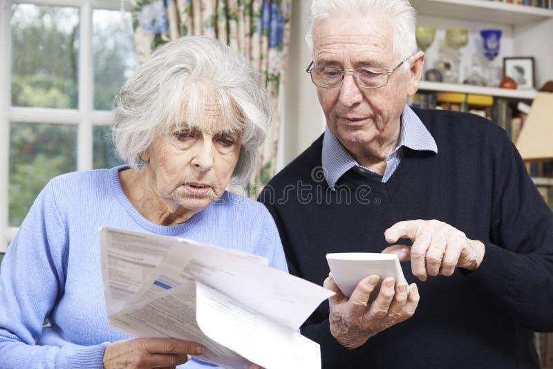 Pares mayores en casa con las cuentas preocupantes de las finanzas caseras imagenes de archivo