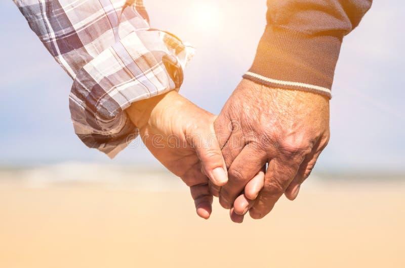 Pares mayores en el amor que camina en la playa que lleva a cabo las manos imagenes de archivo